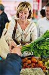 Femme de payer pour des légumes au marché