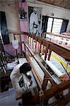 Homme travaillant un métier à tisser dans un village de tissage atelier sous une grande photo du Mahatma Gandhi, Kalna, West Bengal, Inde, Asie