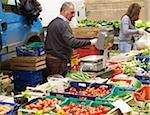 vendors sell vegetables at village farmers market, Cortona, Italy