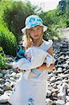 Portrait of Girl Walking Along Rocky Riverbank