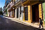Woman Walking Past Brightly-Colored Buildings, Havana, Cuba