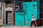 Man Walking Past Brightly-Colored Building, Havana, Cuba