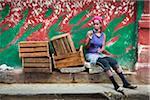 Smoking Woman Sitting Beside Empty Crates on Curb, Havana, Cuba