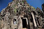 Man looking out a stone window at Angkor Wat, Cambodia