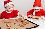 Brother and sister wearing Santa hats and baking