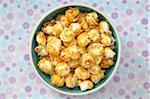 Overhead View of Caramel Popcorn in Bowl on Purple Polka Dot Background, Studio Shot
