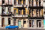 Blue Classic Car Driving Past Residential Apartment Buildings, Havana, Cuba