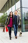 Couple walking dog on city street