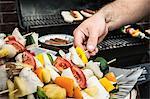 Man grilling vegetable skewers
