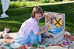 Girl unpacking picnic basket in field