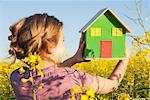 Girl holding model house in field
