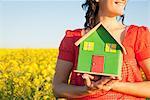 Woman holding model house in field