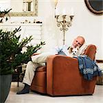 Older man sleeping by Christmas tree