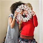 Girls peeking through Christmas wreath
