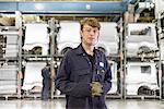 Apprentice standing in car factory