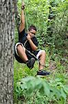 Hispanic boy swings on rope in forest