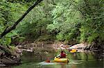 Hispanic boy kayaking in forested creek