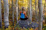 Woman practicing yoga in outdoor aspen grove