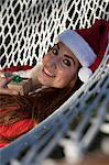 Woman wearing santa hat and lying on hammock