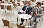 Businessmen meeting at sidewalk cafe