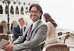 Portrait of smiling businessman holding digital tablet at sidewalk cafe in Venice