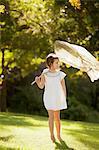 Girl carrying butterfly net in grass