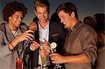 Smiling men toasting cocktails in nightclub