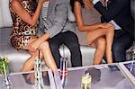 Legs of couples sitting on sofa in nightclub