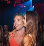 Smiling couple hugging in nightclub