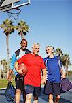 Older men playing basketball on court