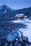 Frozen lake shore and Mountain House at twilight in winter, Popradske Pleso, High Tatras, Slovakia, Europe