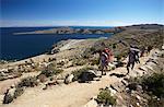 Backpackers hiking on Isla del Sol (Island of the Sun), Lake Titicaca, Bolivia, South America