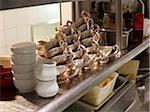 Stacks of silver gravy boats in restaurant kitchen