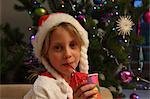 Girl wearing Santa hat by Christmas tree