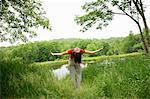 Woman practicing yoga by rural lake