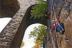 Rock climber scaling brick wall