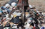 Machinery grabbing waste in landfill
