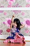 A young girl holding a swirl lollipop aloft
