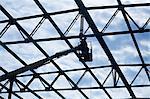 Welder on crane welding roof beam