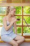 A beautiful woman in a nightie sitting on a window sill drinking tea