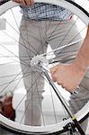 Man fixing bicycle wheel indoors