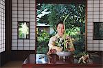 Woman in a kimono performing flower arrangement