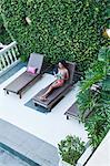 Brazil, Rio de Janeiro city, Gavea, La Maison Hotel, model in a Brazilian bikini sitting on a sun lounger next to the pool in the La Maison boutique hotel MR PR