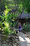 Woman walking through tropical gardens at the Aqua Wellness Resort, Nicaragua, Central America