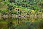 A man paddles his dugout canoe along the shore of Lake Mutanda, Uganda, Africa