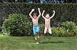 Children jumping in sprinkler