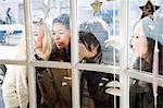 Female friends looking through window