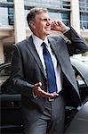 Businessman on cellphone by car