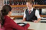 Barman and waitress at bar in restaurant