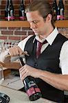 Barman opening bottle of wine
